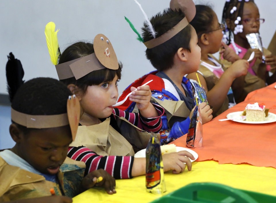 Jocelyn Padilla licks icing from her spoon as she sits at a table with her classmates. Kindergarten students at Eugene Field Elementary School in Oklahoma City have been learning about Thanksgiving traditions and  the history of the national  holiday in America.  Their teachers helped them make paper sack vests and turkey head pieces to wear.  To celebrate the end of the Thanksgiving lesson and reward the students for working so hard, about 80 students in the four kindergarten classes held a pumpkin pie break in the cafeteria Tuesday afternoon, Nov. 20, 2012. The students dressed in their creative paper sack turkey vests and head dresses.   Photo by Jim Beckel, The Oklahoman