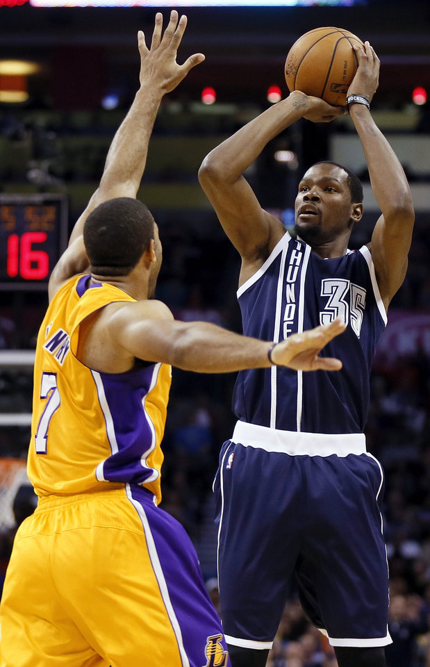 Photo - Oklahoma City's Kevin Durant (35) shoots over LA's Xavier Henry (7) during an NBA basketball game between the Los Angeles Lakers and the Oklahoma City Thunder at Chesapeake Energy Arena in Oklahoma City, Friday, Dec. 13, 2013. Photo by Nate Billings, The Oklahoman