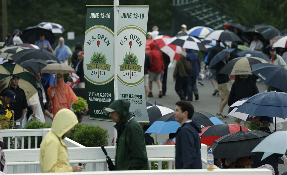 Photo - Spectators walk off the course as weather delays the first round of the U.S. Open golf tournament at Merion Golf Club, Thursday, June 13, 2013, in Ardmore, Pa. (AP Photo/Darron Cummings)