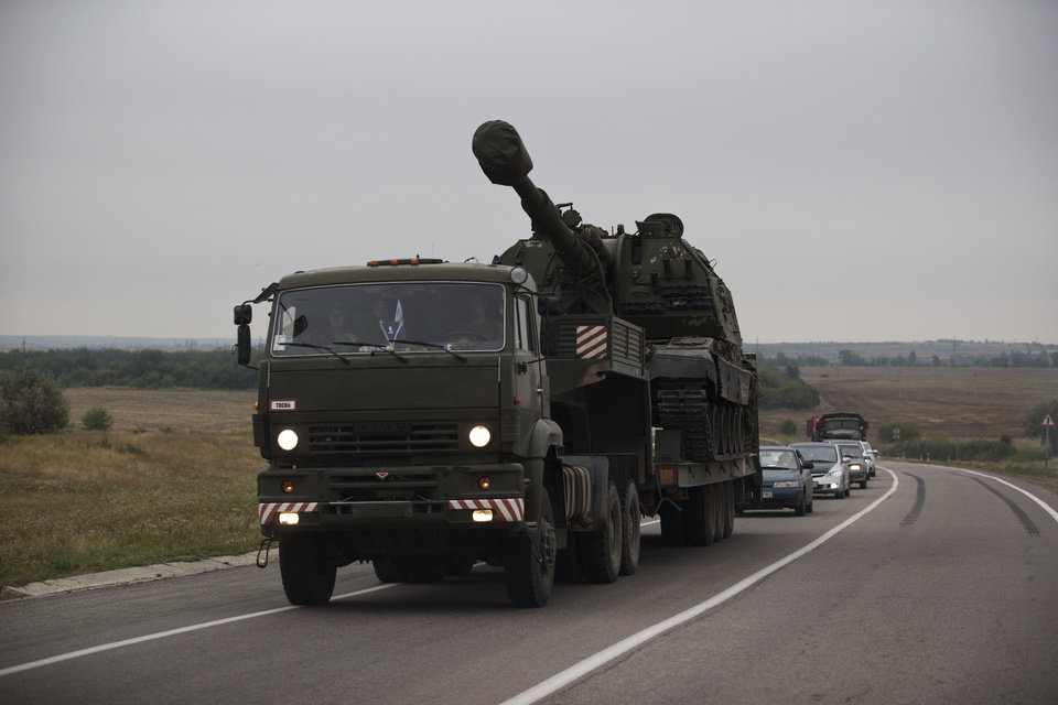 Photo - A Russian military truck carries a MSTA-S self-propelled howitzer about 10 kilometers from the Russia-Ukrainian border control point at town Donetsk, Rostov-on-Don region, Russia, Tuesday, Aug. 19, 2014. Ukrainian government troops were fighting pro-Russian rebels in the streets of Luhansk on Tuesday and captured most of a town near the eastern city of Donetsk, tightening the noose around that key rebel-held stronghold, Ukrainian officials said. (AP Photo/Pavel Golovkin)