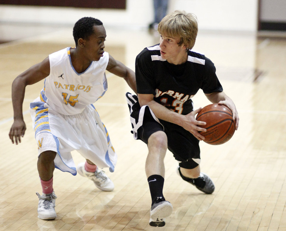 Norman's Grant Ladner looks to pass the ball as Putnam City West's Jujuan Hutchins defends during the boys high school basketball game between Putnam City West and Norman at Edmond Memorial High School, Friday, Feb. 24, 2012. Photo by Sarah Phipps, The Oklahoman
