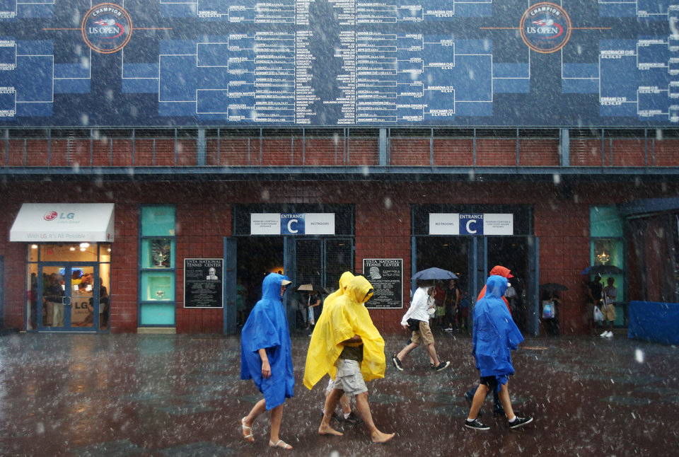 Photo - Tennis fans walk barefoot across the Billie Jean King National Tennis Center as rain falls suspending play during the 2014 U.S. Open tennis tournament, Sunday, Aug. 31, 2014, in New York. (AP Photo/John Minchillo)