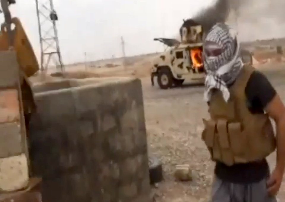 Photo - This image made from video posted by Iraqi0Revolution, a group supporting the al-Qaida breakaway Islamic State of Iraq and the Levant (ISIL) on Wednesday, June 12, 2014, which has been verified and is consistent with other AP reporting, shows a militant standing in front of a burning Iraqi Army Humvee in Tikrit, Iraq. The al-Qaida-inspired group that led the charge in capturing two key Sunni-dominated cities in Iraq this week has vowed to march on to Baghdad, raising fears about the Shiite-led government's ability to slow the assault following lightening gains. Fighters from ISIL on Wednesday took Saddam Hussein's hometown of Tikrit, as soldiers and security forces abandoned their posts and yielded ground once controlled by U.S. forces. (AP Photo/Iraqi0Revolution via AP video)