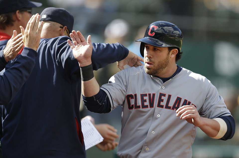 Photo - Cleveland Indians second baseman Jason Kipnis is congratulated after scoring against the Oakland Athletics in the ninth inning of a baseball game Wednesday, April 2, 2014, in Oakland, Calif. Kipnis scored on a single by Carlos Santana. (AP Photo/Ben Margot)