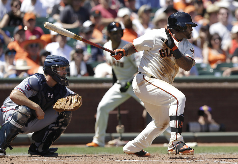Photo - San Francisco Giants' Pablo Sandoval follows through on a single that scored Hunter Pence, next to Atlanta Braves catcher Evan Gattis during the fourth inning of a baseball game in San Francisco, Wednesday, May 14, 2014. (AP Photo)