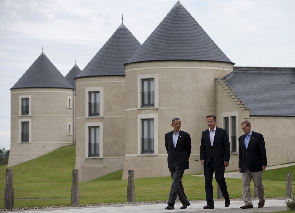 Photo - President Barack Obama walks with British Prime Minister David Cameron, center, and Irish Prime Minister Enda Kenny at the site of the G-8 summit in Enniskillen, Northern Ireland, Tuesday, June 18, 2013. The final day of the G-8 summit of wealthy nations is ending with discussions on globe-trotting corporate tax dodgers, a lunch with leaders from Africa, and suspense over whether Russia and Western leaders can avoid diplomatic fireworks over their deadlock on Syria's civil war. (AP Photo/Evan Vucci)