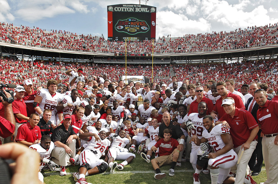 Photo - The Sooners pose for a team photo after defeating Texas 55-17 during the Red River Rivalry college football game between the University of Oklahoma Sooners (OU) and the University of Texas Longhorns (UT) at the Cotton Bowl in Dallas, Saturday, Oct. 8, 2011. Photo by Chris Landsberger, The Oklahoman