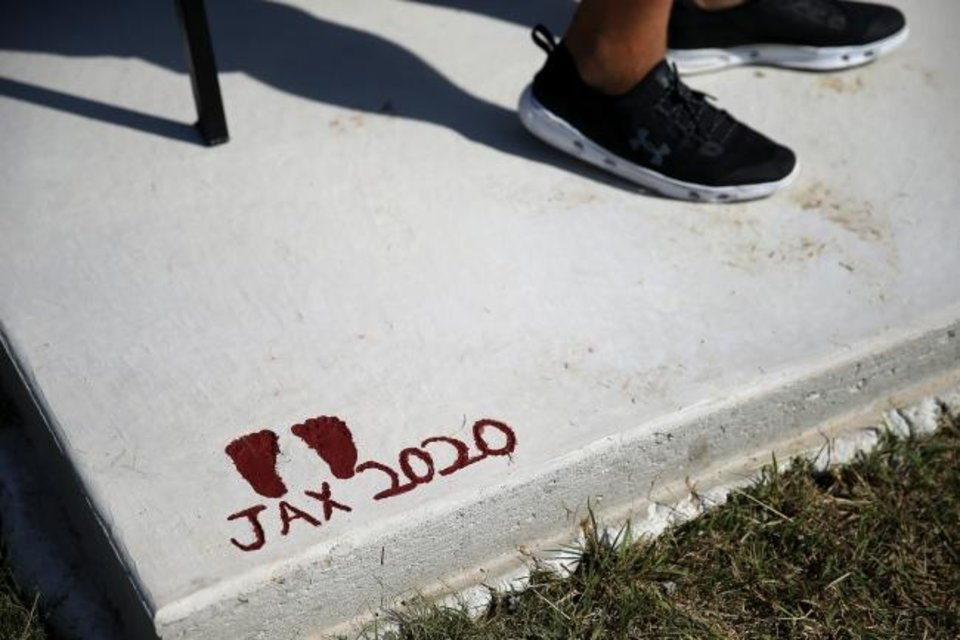 Photo -  2-month-old Jaxon Cochran's footprints are on the concrete slab holding the bench dedicated to his mom, Jacie, who died during childbirth in July. [Bryan Terry/The Oklahoman]