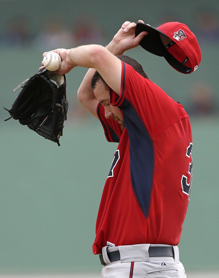 Photo - Minnesota Twins starting pitcher Mike Pelfrey wipes his brow on the mound during the third inning of an exhibition baseball game against the Boston Red Sox in Fort Myers, Fla., Saturday, March 29, 2014. (AP Photo/Gerald Herbert)