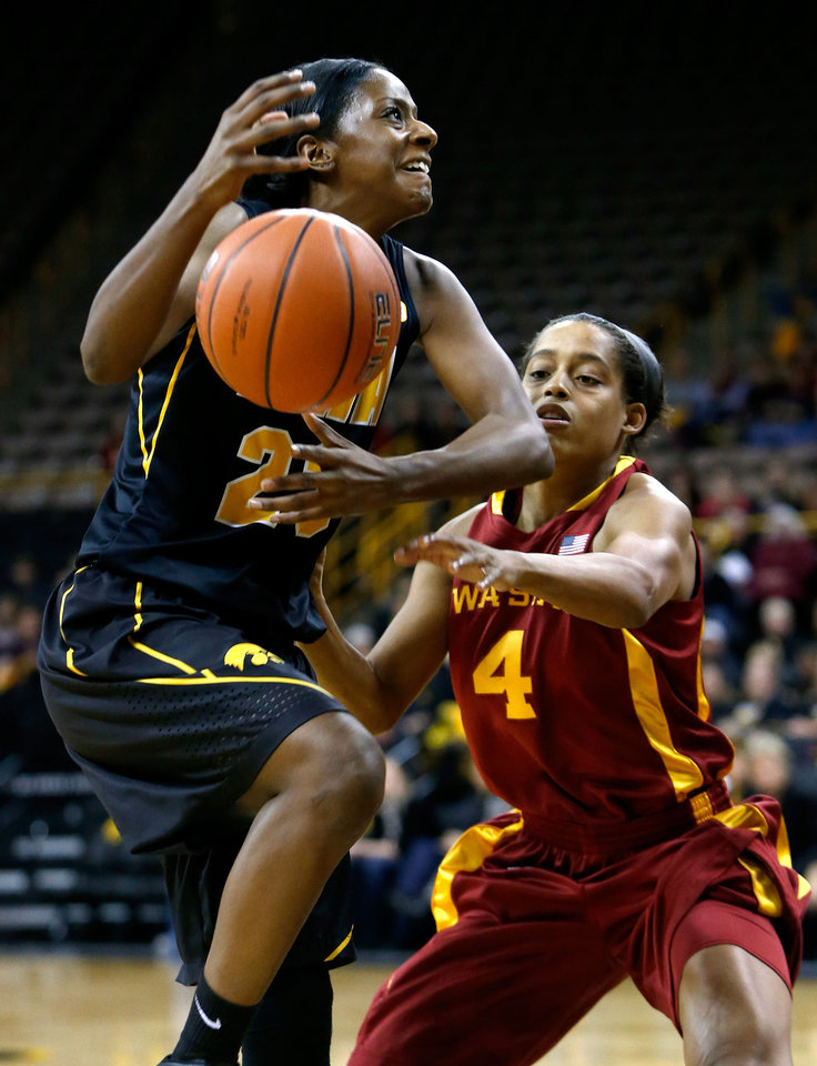 Photo - Iowa guard Theairra Taylor (23) has the ball knocked away by Iowa State guard Nikki Moody (4) as she drives to the hoop during the first half an NCAA college basketball game Thursday, Dec. 6, 2012 at Carver-Hawkeye Arena in Iowa City, Iowa.  (AP Photo/The Gazette,Brian Ray)