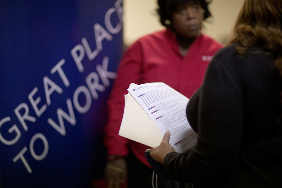 Photo - FILE - In this  Thursday, Nov. 14, 2013, file photo, Jimmetta Smith, of Lithonia, Ga., right, the wife of a U.S. Marine veteran, holds her resume while talking with Rhonda Knight, a senior recruiter for Delta airlines, at a job fair for veterans and family members at the VFW Post 2681, in Marietta, Ga.  The Labor Department issues the November jobs report on Friday, Dec. 6, 2013.  (AP Photo/David Goldman, File)