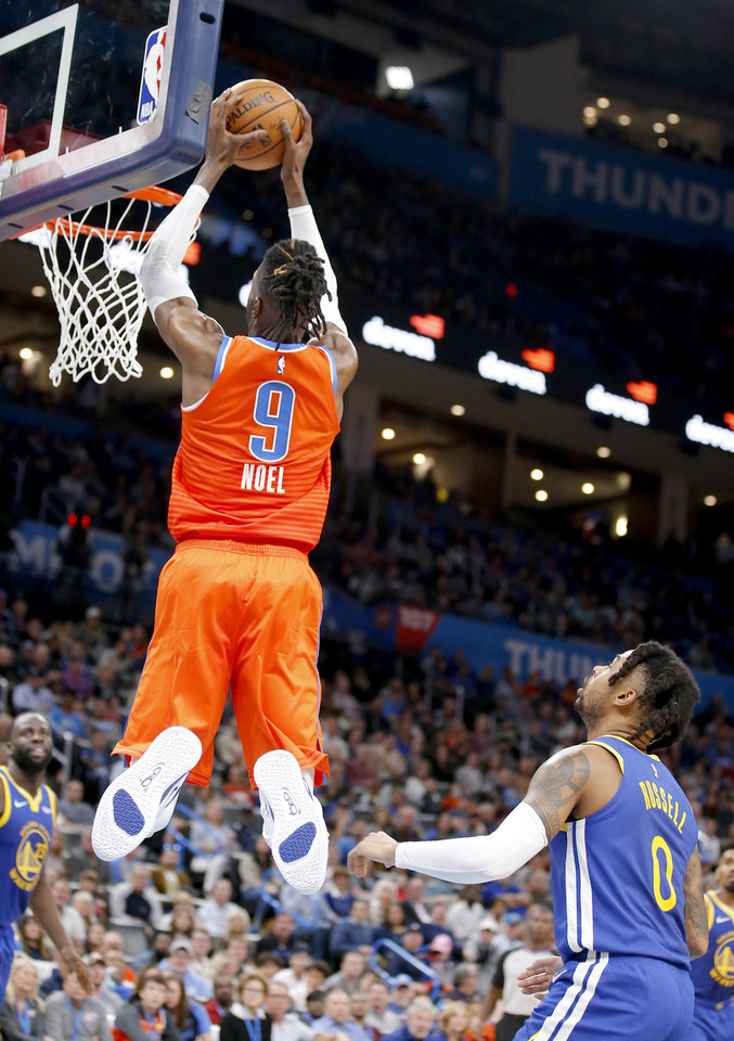 Photo - Oklahoma City's Nerlens Noel (9) dunks the ball in front of Golden State's D'Angelo Russell (0) during the NBA game between the Oklahoma City Thunder and Golden State Warriors at Chesapeake Energy Arena,  Sunday, Oct. 27, 2019. [Sarah Phipps/The Oklahoman]