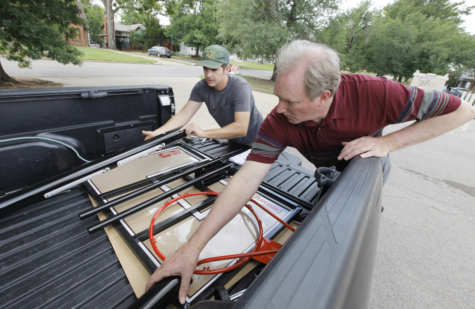 Photo - J. J. Gourley, Westminster Presbyterian Church deacon, and Lee Cosby, Eagle Ridge community relations, unload parts to begin putting together a basketball goal donated to a family raising foster children.  Photos by Paul B. Southerland, The Oklahoman  PAUL B. SOUTHERLAND -  PAUL B. SOUTHERLAND