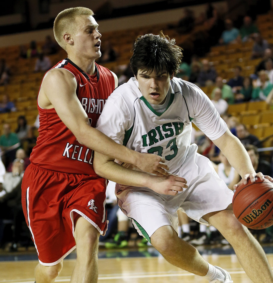 Photo - Will Lienhard (33) of Bishop McGuinness drives the ball against Matt Craig (24) of Bishop Kelley during a Class 5A boys semifinal game in the state basketball championship tournament between Bishop McGuinness and Bishop Kelley at the Mabee Center in Tulsa, Okla., Friday, March 14, 2014. Photo by Nate Billings, The Oklahoman