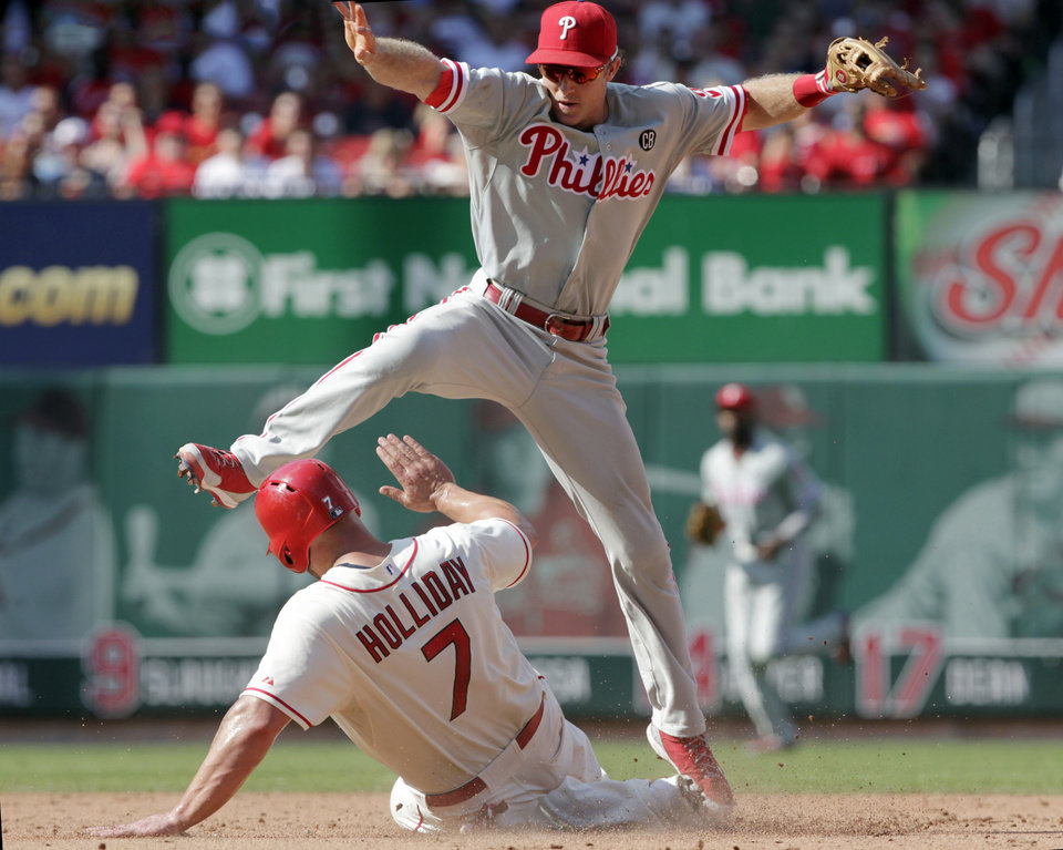 Photo - Philadelphia Phillies second baseman Chase Utley leaps to avoid a sliding St. Louis Cardinals' Matt Holliday (7) after forcing him out at second for the front half of a double play in the sixth inning of a baseball game, Saturday, June 21, 2014 in St. Louis. (AP Photo/Tom Gannam)