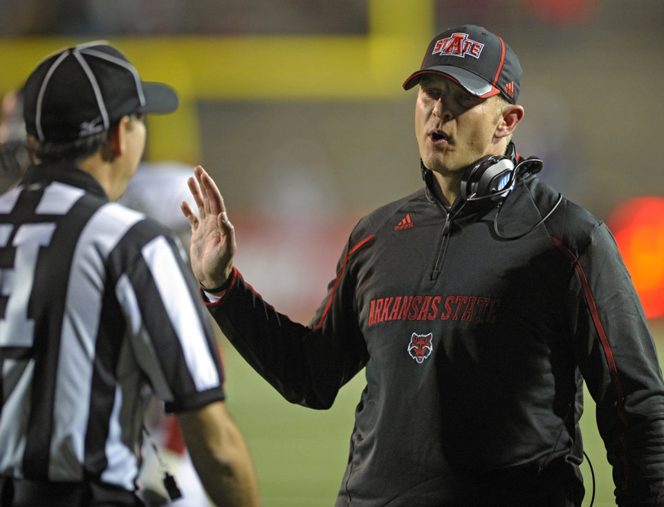 Photo - FILE - In this Nov. 2, 2013 file photo, Arkansas State head coach Bryan Harsin talks with linesman Scott Peterson during a timeout with South Alabama in the second quarter of an NCAA college football game in Mobile, Ala. A person familiar with the decision tells The Associated Press that Boise State has hired  Harsin as its next coach. The person spoke on condition of anonymity because the move had not become official. (AP Photo/G.M. Andrews, File)