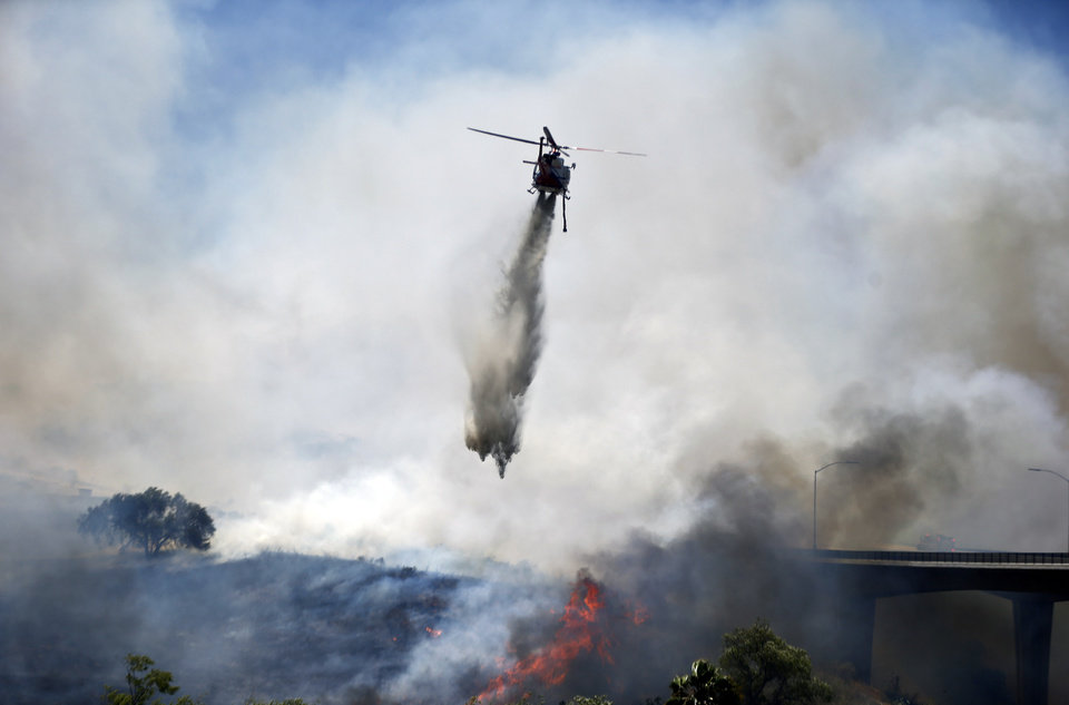 Photo - A helicopter attacks a wild fire burning  Tuesday, May 13, 2014, in San Diego. Wildfires destroyed a home and forced the evacuation of several others Tuesday in California as a high-pressure system brought unseasonable heat and gusty winds to a parched state that should be in the middle of its rainy season. (AP Photo)