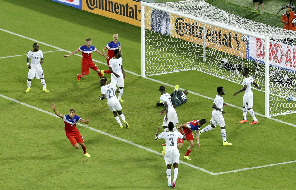 Photo - United States' John Brooks, bottom left, celebrates scoring his side's second goal during the group G World Cup soccer match between Ghana and the United States at the Arena das Dunas in Natal, Brazil, Monday, June 16, 2014. The United States defeated Ghana 2-1. (AP Photo/Hassan Ammar)
