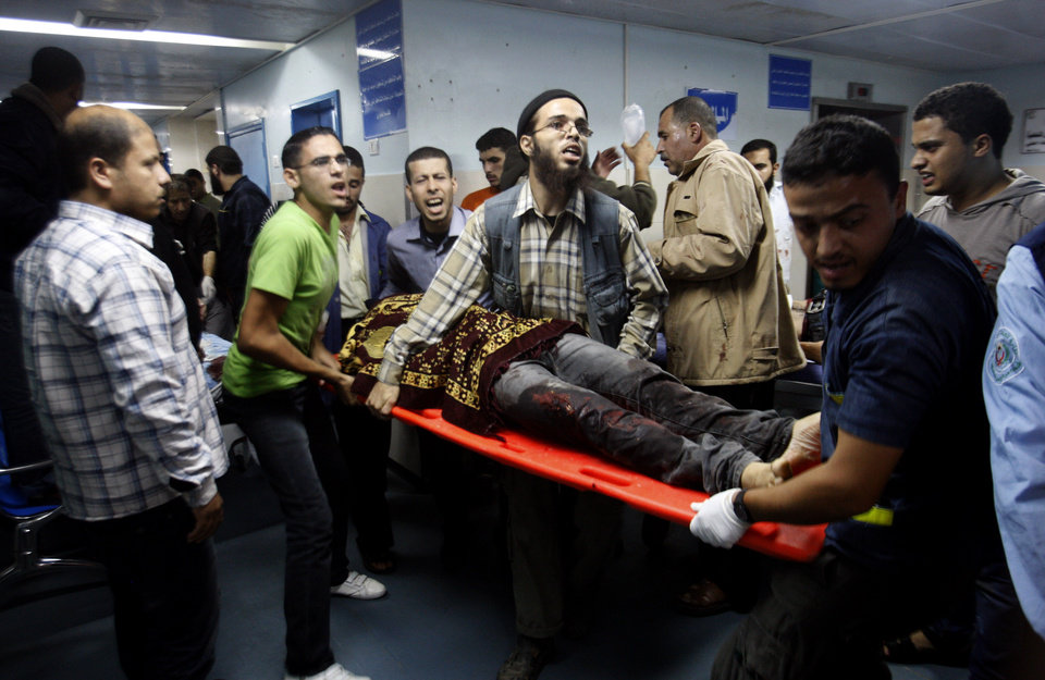 Photo -   Palestinians bring a wounded man to a hospital in Gaza City, Saturday, Nov. 10, 2012. An explosion targeted an Israeli military vehicle on the Jewish state's border with Gaza on Saturday and Israeli troops fired into the Palestinian territory, killing several civilians and wounding at least 25, Gaza officials and witnesses said. (AP Photo/Hatem Moussa)