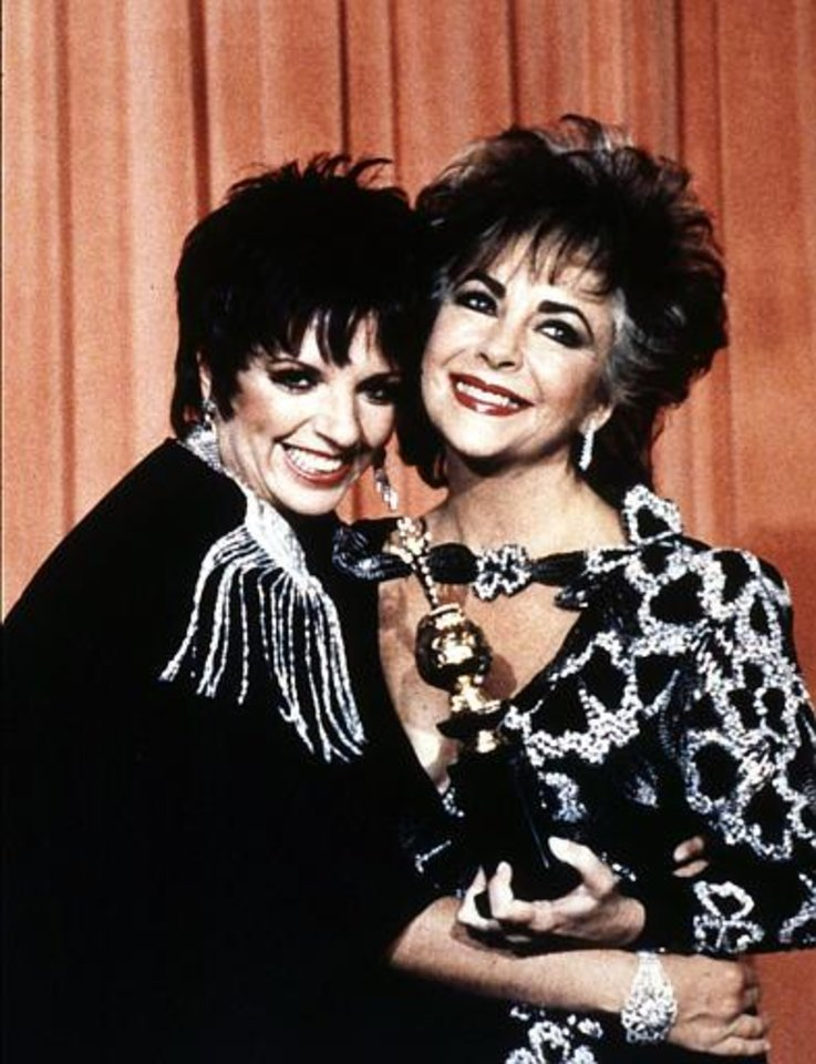 British actress Elizabeth Taylor poses with Liza Minnelli whilst holding her prestigious 'Cecil B. DeMille' award, granted for her contribution to the entertainment industry at the 42nd Golden Globe awards ceremony in Beverly Hills, Ca., Jan. 1985. (AP Photo/Liu Heing Shing)