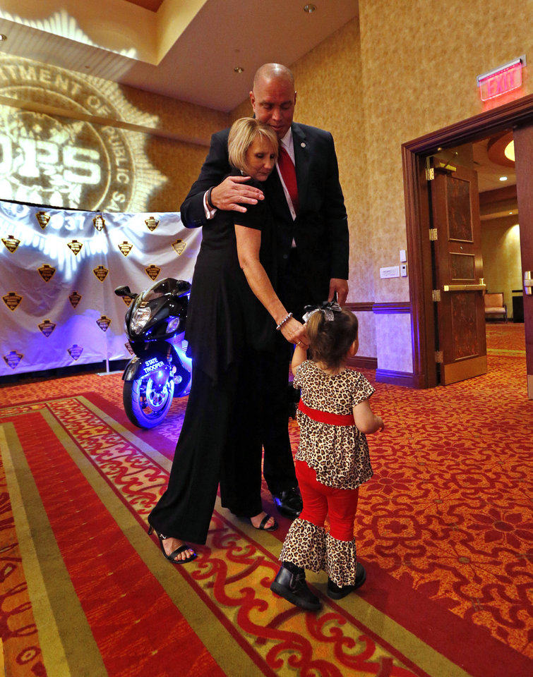 Photo -  Commissioner of Public Safety Michael C. Thompson hugs trooper Nicholas Dees' mother-in-law, Sandra Smith Rudisill, and Dees' daughter Piper, 2, after the unveiling of a plaque as Dees is honored Wednesday during the Trooper of the Year Awards in Norman. Photo by Steve Sisney, The Oklahoman   STEVE SISNEY -  THE OKLAHOMAN