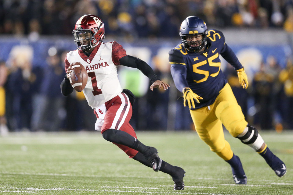 Photo - Oklahoma Sooners quarterback Kyler Murray (1) dodges an attempted tackle by West Virginia Mountaineers defensive lineman Dante Stills (55) during the NCAA football game between the Oklahoma Sooners and the West Virginia Mountaineers at Mountaineer Field at Milan Puskar Stadium in Morgantown, W.Va on Friday, November 23, 2018. IAN MAULE/Tulsa World