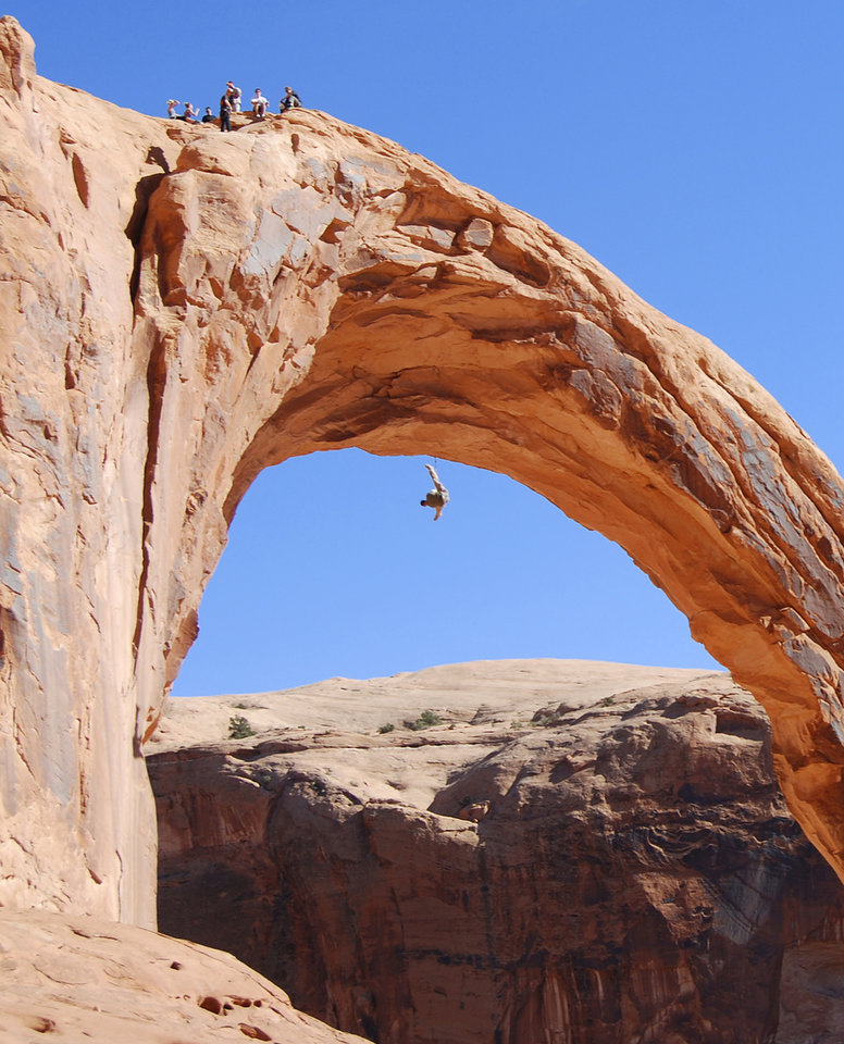 Photo - FILE - This Nov. 4, 2012, file photo, shows a person swinging from the Corona Arch near Moab, Utah. The federal government is asking for people to weigh in on whether it should temporarily ban daredevil rope swinging and other activities from iconic arches in Moab. The Bureau of Land Management says rope recreation at Corona Arch and Gemini Bridges may be disturbing other people in popular hiking areas that each get more than 40,000 visitors a year. The BLM is accepting written and emailed comments through Sept. 25, 2014. (AP Photo/The Salt Lake Tribune, Brian Maffly, File)