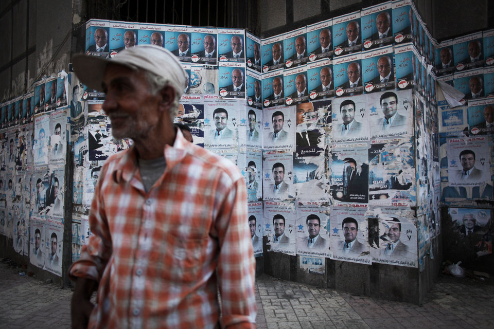 Photo -   An Egyptian man stands beside a polling station filled with political posters during the second day of the presidential election runoff in Cairo, Egypt, Sunday, June 17, 2012. Egyptians are choosing between a conservative Islamist and Hosni Mubarak's ex-prime minister in a second day of a presidential runoff that has been overshadowed by the domination of the country's military. (AP Photo/Manu Brabo)