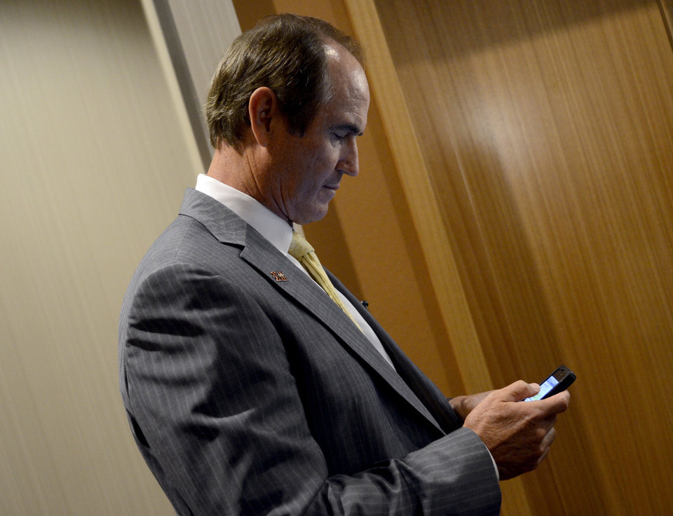 Photo - Baylor head coach Art Briles checks his phone while walking between stations during NCAA college football Big 12 Media Days, Monday, July 25, 2011, in Dallas. (AP Photo/Matt Strasen)