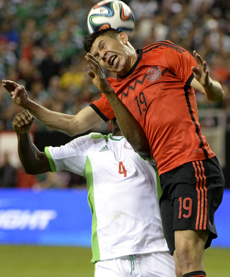 Photo - Mexico's Oribe Peralta (19) heads the ball in front of Nigeria's Kenneth Omeruo (4) during the first half of an international friendly soccer match Wednesday, March 5, 2014, in Atlanta. (AP Photo/David Tulis)