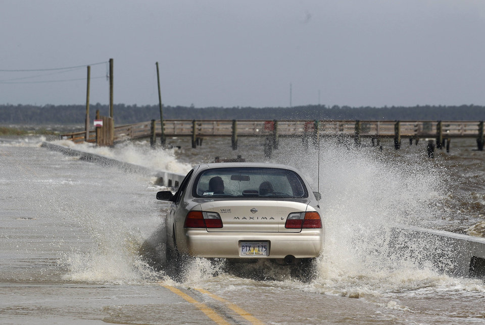 A motorist drives through a flooded street on Tuesday, Aug. 28, 2012, in Bay St. Louis, Miss.  The U.S. National Hurricane Center in Miami said Isaac became a Category 1 hurricane Tuesday with winds of 75 mph. It could get stronger by the time it's expected to reach the swampy coast of southeast Louisiana. (AP Photo/John Bazemore) ORG XMIT: MSJB105
