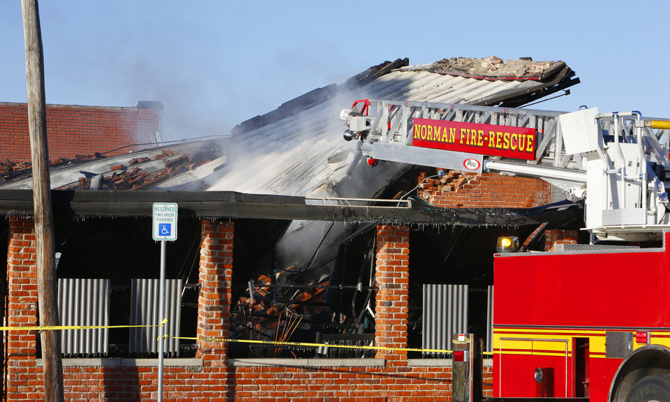 Photo - The roof collapses Monday at S & B Burger Joint in downtown Norman after an early morning fire destroyed the landmark building.  PHOTO BY  PAUL B. SOUTHERLAND,  THE OKLAHOMAN  PAUL B. SOUTHERLAND -