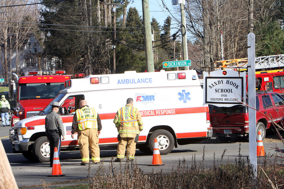 Photo - Ambulances leave the Sandy Hook Elementary School in Newtown, Conn. where authorities say a gunman opened fire, leaving 27 people dead, including 20 children, Friday, Dec. 14, 2012.(AP Photo/The Journal News, Frank Becerra Jr.) MANDATORY CREDIT, NYC OUT, NO SALES, TV OUT, NEWSDAY OUT; MAGS OUT ORG XMIT: NYWHI114