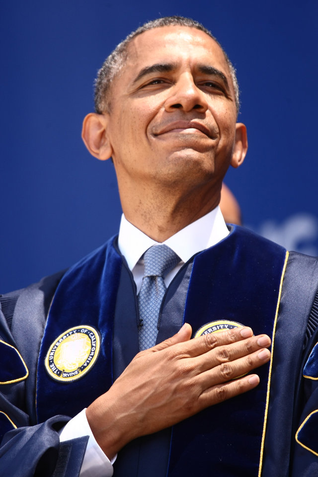 Photo - President Barack Obama puts his hand over his heart during the pledge of allegiance before he gives the commencement speech for the University of California, Irvine at the Angel Stadium in Anaheim, Calif., Saturday, June 14,  2014.    (AP Photo/Los Angeles Times, Genaro Molina, Pool)