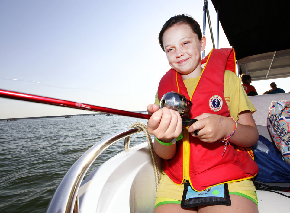 Photo - Izzy Mauldin , 11  fishes from the front of the boat during Camp Cavett at Lake Texoma.   David McDaniel - The Oklahoman