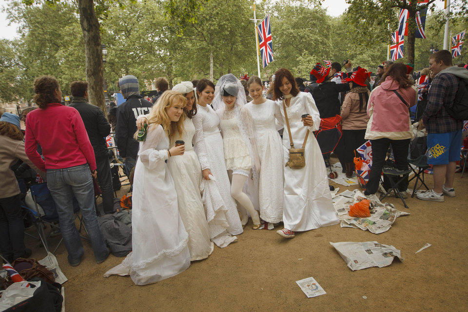 Photo - Royal enthusiasts dressed as brides wait at the Mall area before Britain's Prince William and Kate Middleton wedding in London, Friday, April 29, 2011. (AP Photo/Daniel Ochoa de Olza) ORG XMIT: DO109
