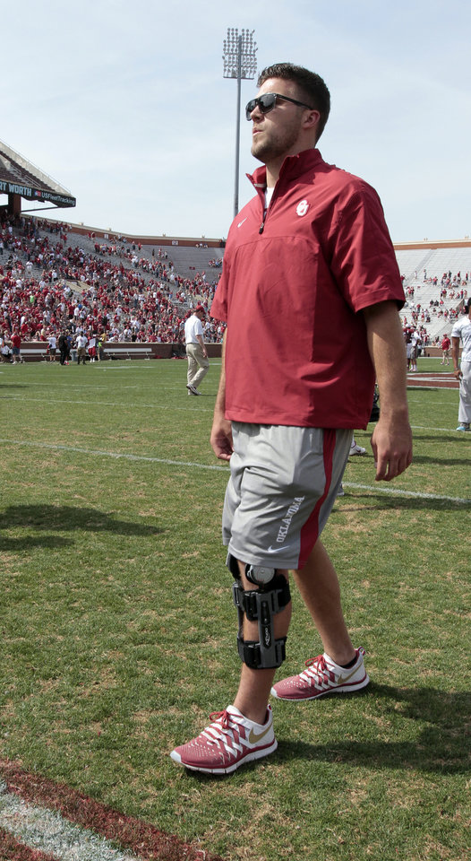 Blake Bell walks wearing a brace during the Spring College Football Game of the University of Oklahoma Sooners (OU) at Gaylord Family-Oklahoma Memorial Stadium in Norman, Okla., on Saturday, April 12, 2014.  Photo by Steve Sisney, The Oklahoman