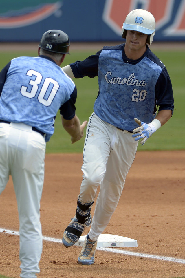 Photo - North Carolina's Skye Bolt (20) is congratulated by manager Mike Fox as he rounds third base after hitting a two-run home run during the first inning of an NCAA college baseball regional tournament game against Long Beach State in Gainesville, Fla., Sunday, June 1, 2014. (AP Photo/Phelan M. Ebenhack)