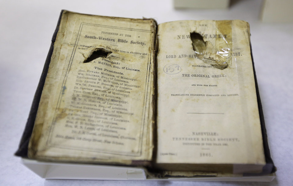 "Photo - The bible belonging to Confederate soldier C. Robey, who was wounded on the third day of Gettysburg battle, is prepared for display in a work room at the museum of the Confederacy in Richmond, Va., Wednesday, May 1, 2013. The Museum of the Confederacy will open the exhibit ""Gettysburg: They walked through blood"" on May 11 to commemorate the 150th anniversary of the Battle of Gettysburg. (AP Photo/Steve Helber)"