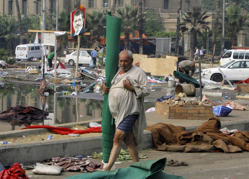 Photo - An Egyptian walks among the debris of a protest camp in Nahda Square, Giza, Cairo, Egypt, Thursday, Aug. 15, 2013. Egypt faced a new phase of uncertainty on Thursday after the bloodiest day since its Arab Spring began, with nearly 300 people reported killed and thousands injured as police smashed two protest camps of supporters of the deposed Islamist president. Wednesday's raids touched off day-long street violence that prompted the military-backed interim leaders to impose a state of emergency and curfew, and drew widespread condemnation from the Muslim world and the West, including the United States.  (AP Photo/Amr Nabil)