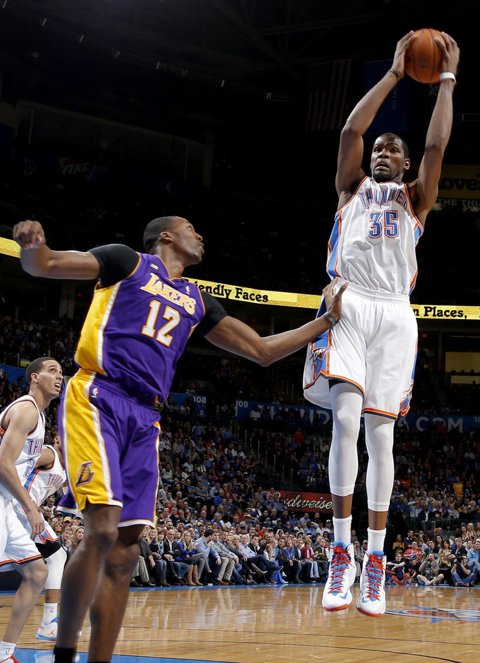 Photo - Oklahoma City's Kevin Durant (35) grabs a rebound beside Los Angeles' Dwight Howard (12) during an NBA basketball game between the Oklahoma City Thunder and the Los Angeles Lakers at Chesapeake Energy Arena in Oklahoma City, Tuesday, March. 5, 2013. Photo by Bryan Terry, The Oklahoman