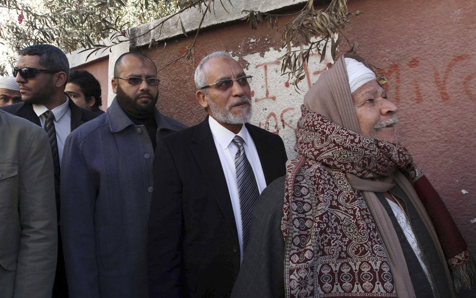 Photo - FILE - In this Saturday, Dec. 22, 2012  file photo, Muslim Brotherhood leader Mohammed Badie, second right, waits in line outside a polling place in Beni Suef, Egypt, to vote on a constitution drafted by Islamist supporters of President Mohammed Morsi. Badie, the Muslim Brotherhood's spiritual leader and over 180 others were sentenced to death Saturday, June 21, 2014 by an Egyptian court in the latest mass trial following last year's overthrow of the country's Islamist president. The ruling by the southern Minya Criminal Court is the largest confirmed mass death sentence to be handed down in Egypt in recent memory and comes from Judge Said Youssef, who earlier presided over the mass trial. It is the second death sentence for Badie since the crackdown against his group began. (AP Photo/Ahmed Ramadan, File)