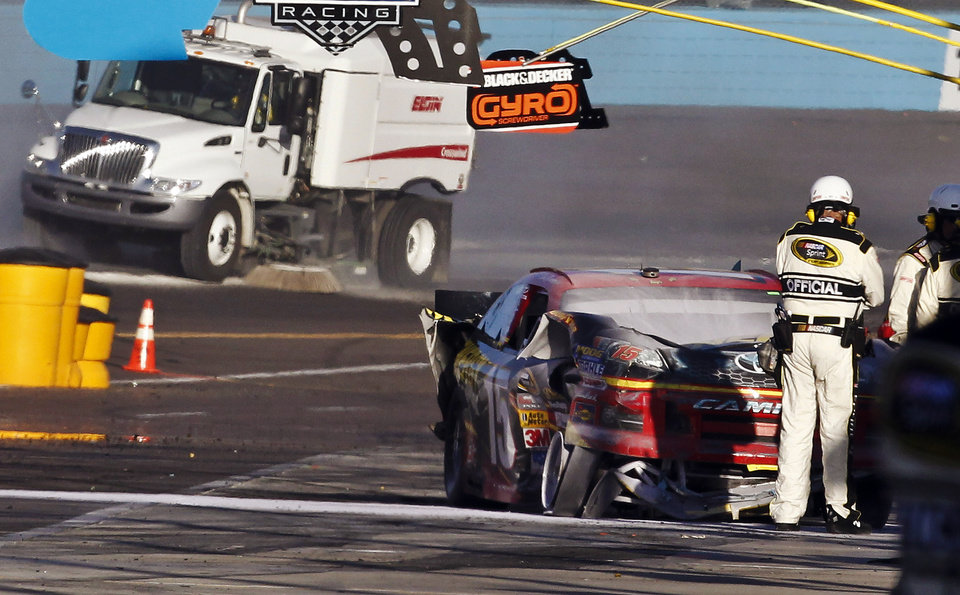 Photo -   An official looks over Clint Bowyer's wrecked car as it rests on pit road after a collision with Jeff Gordon during a NASCAR Sprint Cup Series auto race at Phoenix International Raceway, Sunday, Nov. 11, 2012, in Avondale, Ariz. (AP Photo/Ross D. Franklin)