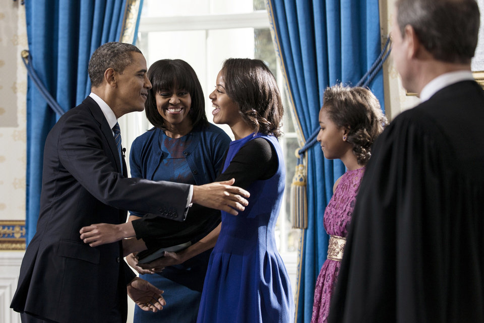 President Barack Obama embraces daughter Malia as first lady Michelle Obama and daughter Sasha, right,  and Supreme Court Chief Justice John Roberts, Jr., look on after the official swearing-in in the Blue Room of the White House, Sunday, January 20, 2013 in Washington.  (AP Photo/Brendan Smialowski, Pool) ORG XMIT: WX108