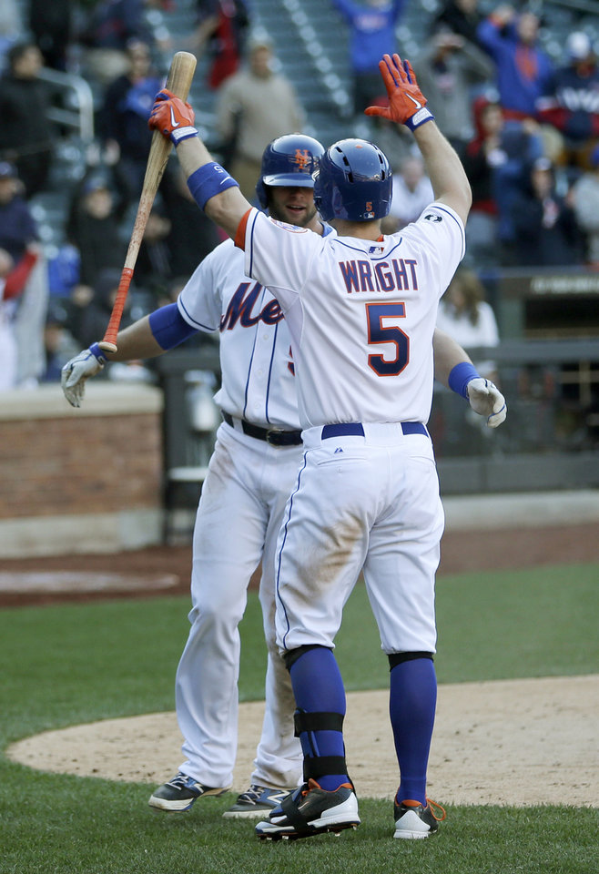Photo - New York Mets' Kirk Nieuwenhuis, left, celebrates with David Wright after scoring on a sacrifice fly hit by Curtis Granderson during the fourteenth inning of the baseball game at Citi Field, Sunday, April 20, 2014 in New York. The Mets defeated the Braves in extra innings 4-3. (AP Photo/Seth Wenig)