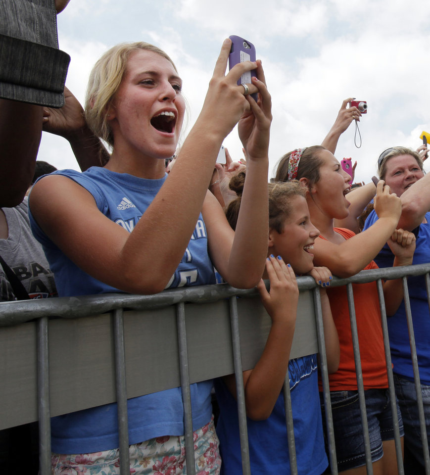 Photo - Fans cheer as the Thunder arrives at a welcome home rally for the Oklahoma City Thunder in a field at Will Rogers World Airport after the team's loss to the Miami Heat in the NBA Finals, Friday, June 22, 2012. Photo by Nate Billings, The Oklahoman