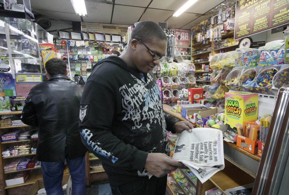 Photo -   Jasen Blackman reads newspaper headlines about President Obama's reelection as he stops at a Coney Island delicatessen, Wednesday, Nov. 9, 2012 in New York. President Barack Obama faces a new urgent task now that he has a second term, working with a status-quo Congress to address an impending financial crisis that economists say could send the country back into recession. Coney Island was hard hit by Superstorm Sandy. (AP Photo/Mark Lennihan)