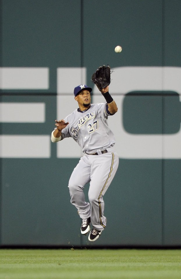 Photo - Milwaukee Brewers center fielder Carlos Gomez (27) jumps up to catch a line drive by Washington Nationals' Wilson Ramos for an out during the fourth inning of a baseball game, Friday, July 18, 2014, in Washington. (AP Photo/Nick Wass)