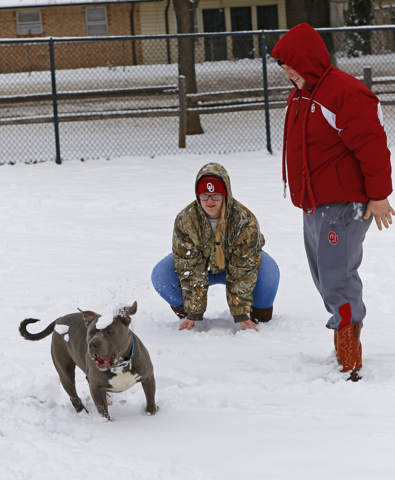 Photo - Shelby Jones and Kyle Colton play with their dog, Boomer, in the dog park at Bickham Rudkin Park in Edmond, Wednesday, February 5, 2020.  [Photo by Doug Hoke/The Oklahoman]