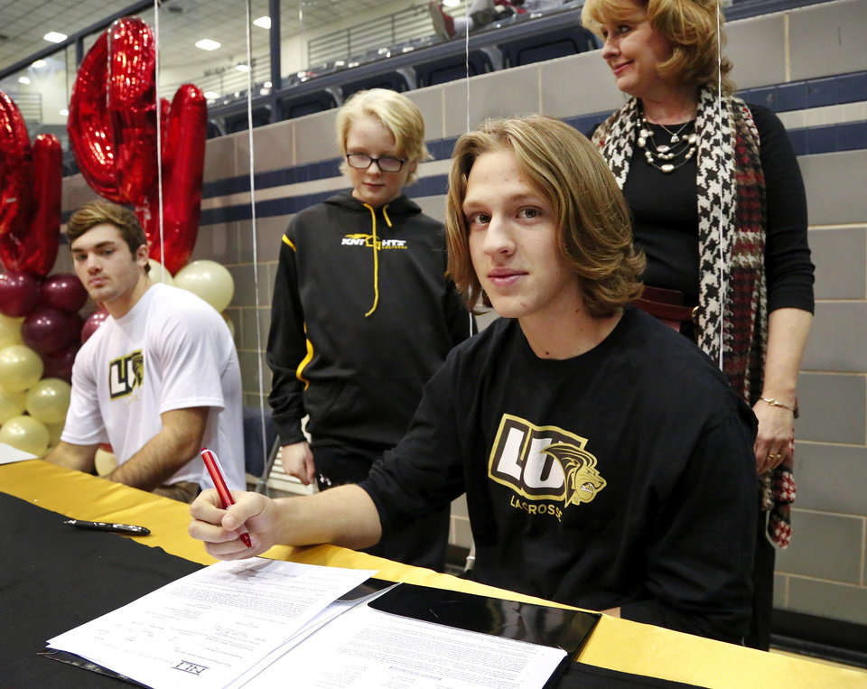 Sam Heaton, foreground, and Jake Hobbs, background, signed letters to play lacrosse at Lindenwood. Athletes from Edmond North High School signed national letters of intent with colleges and universities during a ceremony in the school\'s gymnasium Wednesday morning, Nov. 13, 2013. Various sports include golf, softball, wrestling, lacrosse and others. Photo by Jim Beckel, The Oklahoman